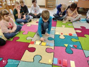 MISIAKI - Chłopiec przeliczający figury geometryczne na dywanie